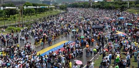 """""""PLANTÓN"""" EN CARACAS. Cubriéndose con paraguas o capas de la lluvia que ha caído de forma intermitente, miles de personas estuvieron apostadas en la neurálgica autopista Francisco Fajardo, en el este de Caracas."""